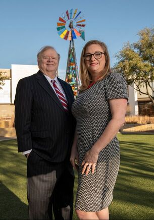 Rod Tanner and Jamie Gilmore, Attorneys at Tanner & Associates, P.C., standing in front of a colorful windmill in Fort Worth, Texas